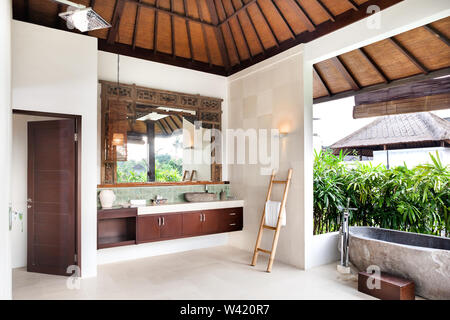 Bathing area from the outside with the wash area that covered with plants, stone or cement basin, tub to shower - Stock Photo