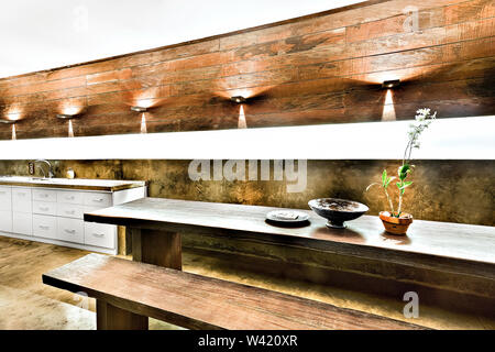 Outdoor dining or patio area with wooden furniture including benches and tables under the flashing lights - Stock Photo