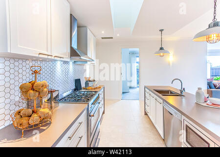 Modern kitchen with fancy items like thread balls on a small rack on the counter which has a stove next to the hallway to the door. There are hanging - Stock Photo