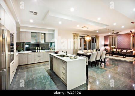 Modern and shiny kitchen with dining and living area, including a counter top and kitchenware on the reflective tiles, there are lights flashing at ni - Stock Photo