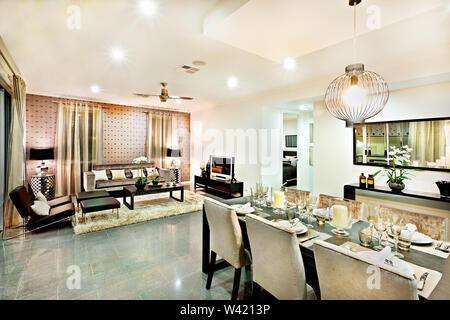 Luxury living room and dining area with hanging lights including chairs and tables beside the television near the carpet and door entrance - Stock Photo