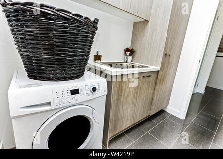 Clean laundry area with front-load washing machine, a laundry basket, cabinets, and a basin - Stock Photo