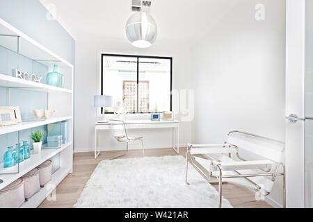 Modern work place with white decoration furniture items including a glass chair and sofa on the wool carpet beside the rack - Stock Photo