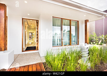 Modern house entrance with wooden door and concrete floor with a grass on the ground - Stock Photo