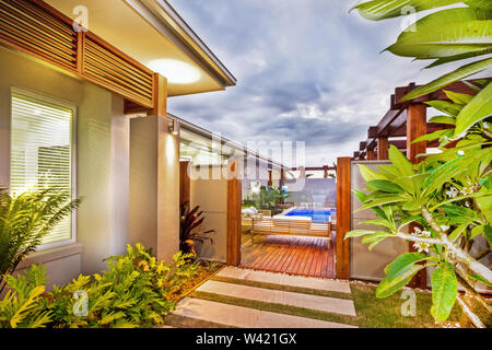 Lavish backyard with tiled and wooden passage, pool view, and sofa set - Stock Photo