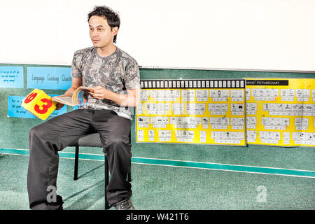 Boy sitting on a chair and reading a book while looking front in a classroom or lab - Stock Photo