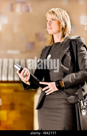 Perfect businesswoman looks forward very confidently and holding files and documents on a blurred background - Stock Photo