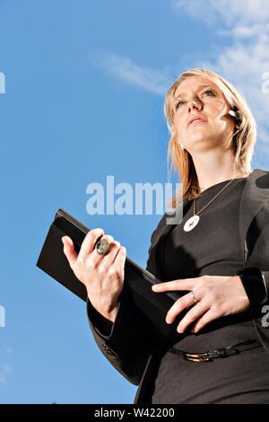 Low angle view of a Businesswoman looking forward confidently and holding books on her hands - Stock Photo