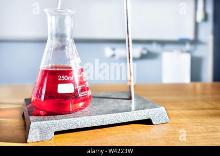 Laboratory equipment on the table in a university, including a beaker with a red color chemical and a supporter - Stock Photo