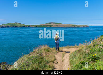 Lone adventurer standing on the cliff top in St Justinians looking out over Ramsey Sound towards Ramsey Island RSPB nature reserve - Stock Photo