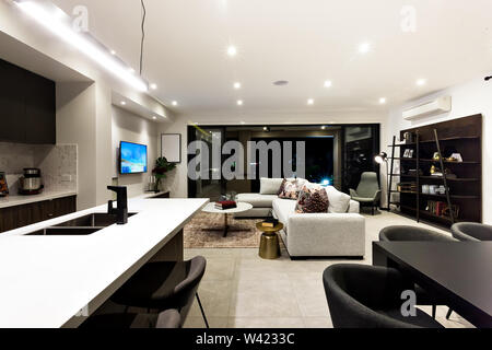 Creative living room including kitchen, dinner, shelf and living room next to outside patio area at night - Stock Photo