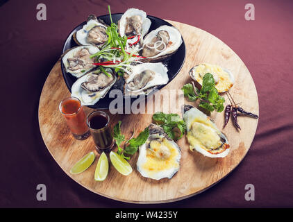 Opened oysters on ice seafood fresh and cooked served with sauce on wooden tray - Stock Photo
