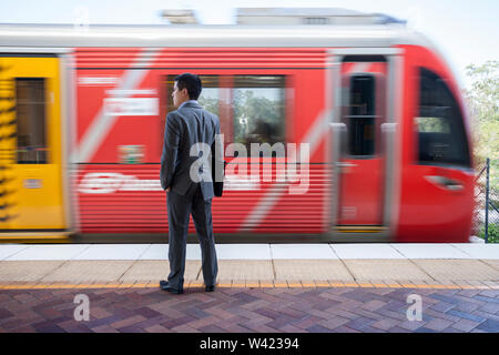 Red color train stopped infront of man, sunlight around the area, morning time and rush hours, floor is tiled, sky is clear. - Stock Photo