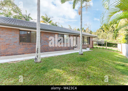 View of the backyard of a house with full grown palm trees and beautiful grass landscape - Stock Photo