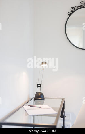 View of a stylish reading table with wrought iron frame featuring a reading lamp and a notebook kept on it - Stock Photo