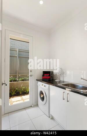 Simply-designed laundry area featuring a sink, a cabinet, and a front-load washing machine - Stock Photo