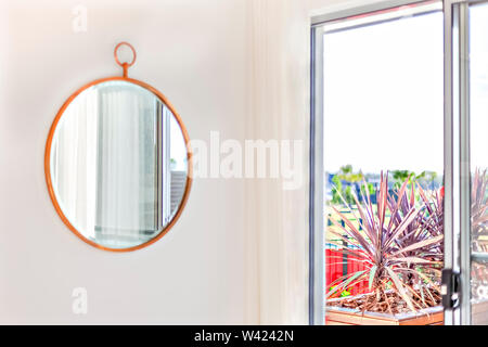 Circle shape mirror with a wooden frame on the wall near the curtain and the window which showed the outside - Stock Photo