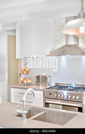 Modern kitchen stove with some fancy items on the counter top, There is blurred tap and sink before the chimney and pantry cupboards on the white wall - Stock Photo