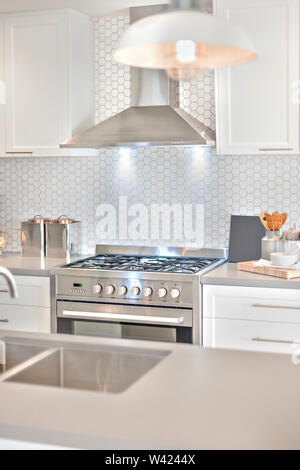 Modern house with a kitchen including a silver and shiny stove and chimney with flashing lights - Stock Photo