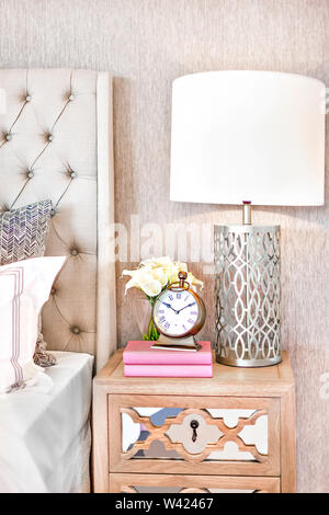 Modern bedroom and table lamp with a clock and flowers on the wooden cabinet with a key hole, colorful pillows on bed, very clean place. - Stock Photo