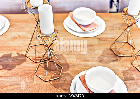 Metal fancy items like gold candelabra on the table with white candles and dining table set up with dishes and mugs. the candle support is like a beve - Stock Photo