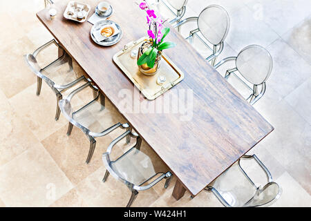 Wooden dining table above view with plastic chairs, the golf color plate and vase holding a purple flowering plants with green leaves beside tea cups - Stock Photo