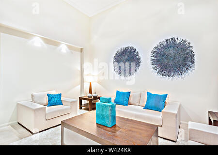 Room with perfect lighting and furnitures, sofa set is white color and have pillows, tables are made in woods,evening time scene. - Stock Photo
