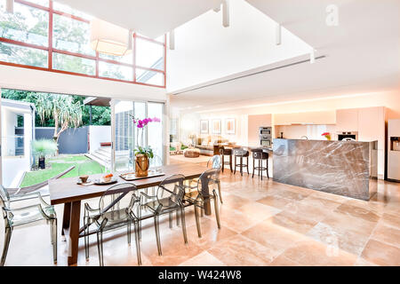 Modern house interior and outdoor including dining and kitchen beside living room, the dining or patio area has a wooden table with plastic see throug - Stock Photo