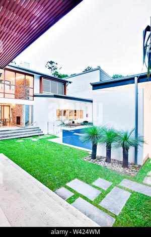 Modern house garden view from the doorstep including a green grass lawn with a pool under a white sky, there is a door entrance to the inside from the - Stock Photo