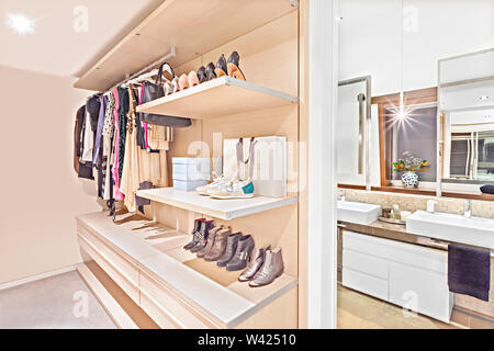 Luxury clothing store of a house or hotel with attached bathroom including shoes for men and women on the rocks beside to the washroom including mirro - Stock Photo