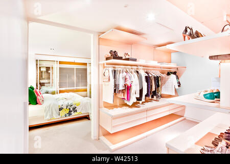 Bedroom attached to the garment store room of a house with ladies and gents shirts  hanging under the racks and shoes on the shelves beside the bedroo - Stock Photo