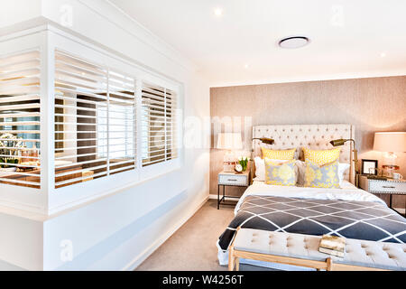 Master bedroom with yellow pillows and attached bathroom with an open window fixed on the white walls, the black blanket on the bed near to flashing t - Stock Photo