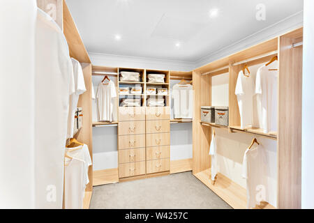 Modern laundry room with white walls and wooden shelves with dress bags, there are drawers with handles, the white ceiling has lights flashing, few sh - Stock Photo
