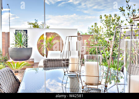 White candles on a glass table under a sunlight view from outdoor like a patio or dining area, the background is blurred and rattan chairs can be seen - Stock Photo