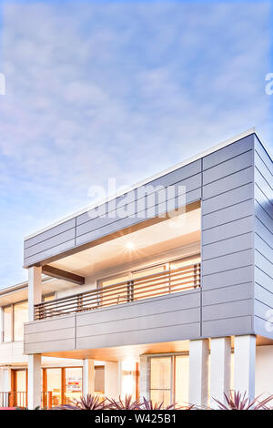 Modern mansion and blue sky with white clouds over lights flashing luxury house or hotel front side, there are glass doors and windows from the facade - Stock Photo