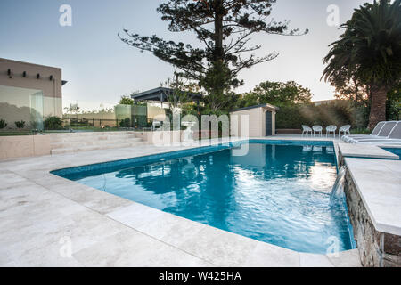 Luxury swimming pool view with blue water poolside with chairs and small fountain from a corner with trees surrounded by a glass wall and trees in the - Stock Photo