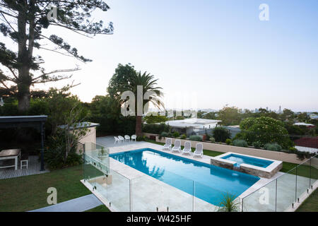 Modern swimming pool area view from a high angle shot which covered with glass panels and tress around, the area is filled with trees and house and it - Stock Photo