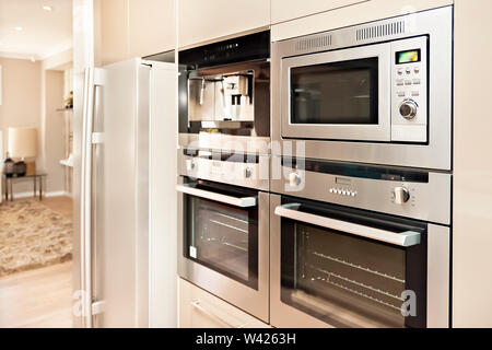 Luxurious kitchenware including silver oven and refrigerator in the kitchen which has a wooden floor, Pantry cupboards are light brown color and insta - Stock Photo