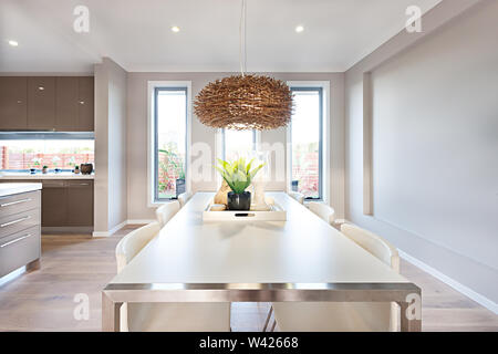 Dinning room has a wooden floor and gray color walls with long glass windows. There is a green plant in a black vase and candles clearly see on the lo - Stock Photo
