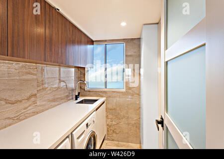 A clean laundry area with cabinets, a basin, and a front-load washing machine - Stock Photo