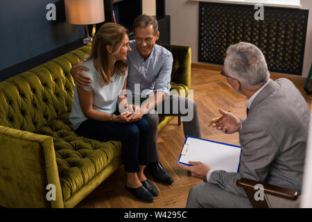 Happy middle-aged married couple sitting on the sofa - Stock Photo