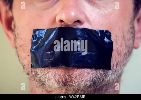 Upset man with self-adhesive tape over her mouth. - Stock Photo