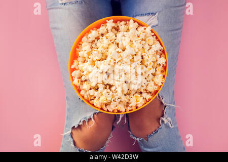 Woman in jeans holding bowl with popcorn over pink background. Food and enternaiment concept - Stock Photo