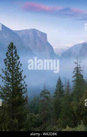 Classic Tunnel View of scenic Yosemite Valley with famous El Capitan and Half Dome rock climbing summits in beautiful misty atmosphere at morning. USA - Stock Photo