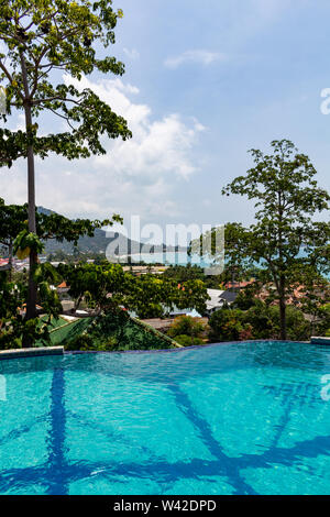 Tropical infinity swimming pool surrounded by green forest on Koh Samui island in Thailand - Stock Photo