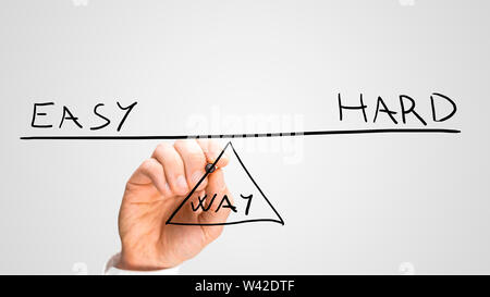 Conceptual image of the hand of a man drawing a seesaw in equilibrium with the text Easy - Hard - Way showing a balance between the two methods of rea - Stock Photo