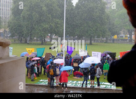 Bristol, UK. 19th July 2019. Rain pours on the Extinction Rebellion youth rally on college Green in Bristol City center. This is the 5th day of the climate change protest in the city. Credit: Mr Standfast/Alamy Live News - Stock Photo