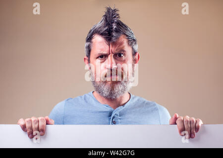 Closeup portrait of an adult man with a beard and iroquois. People and emotions concept - Stock Photo