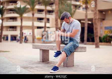 Man suffering from knee pain sitting on bench outdoor. People, health care and medicine concept - Stock Photo