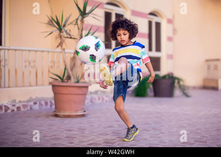 Little boy with curly hair with soccer ball outdoor. Children and entertainment concept - Stock Photo